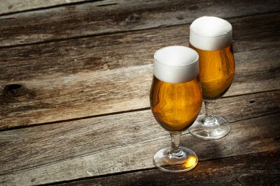 Wall mural Two glass beer on wood background with copyspace