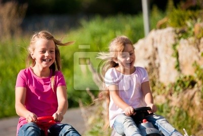 Two sisters with toy cars