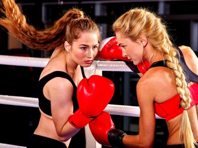 Wall mural Two  women boxer wearing red  gloves to box in ring. Martial arts.