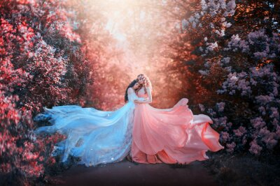 Wall mural two women in long dresses hugging train flies wind. bright fabulous purple colors art retouching processing. Natural cosmetics scented spring flowers tenderness smell perfume. Blonde brunette hair