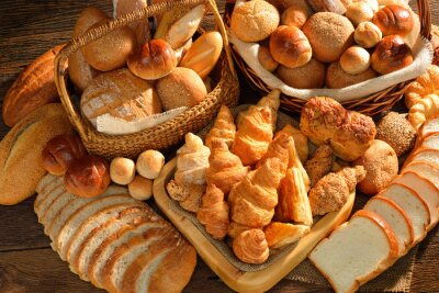 Wall mural Variety of bread in wicker basket on old wooden background.