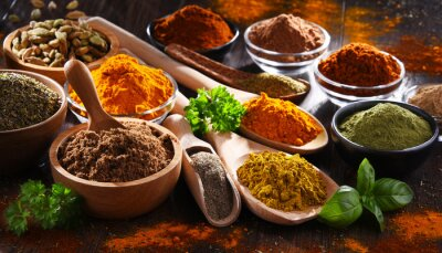 Wall mural Variety of spices on wooden kitchen table.