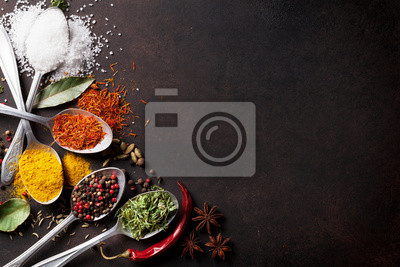 Wall mural Various spices spoons on stone table