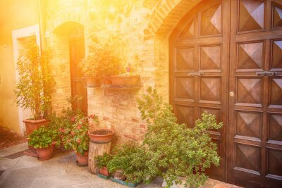 Wall mural View of the ancient old european city. Street of Pienza, Italy with wooden doors. Sunny travel background.