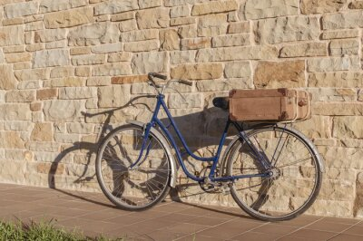 Wall mural Vintage bicycle and old suitcase in a stone wall