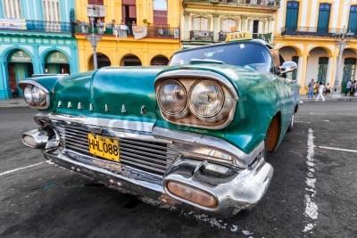 Wall mural Vintage car in a colorful neighborhood in Havana