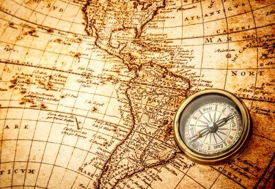 Wall mural Vintage compass lies on an ancient world map.