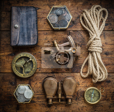 Vintage compass, sextant, binoculars, rope and coins on the old wood table. Adventure stories background. Retro style.
