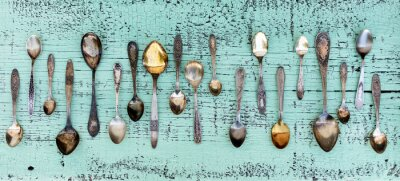 Wall mural Vintage cutlery - spoons, forks and knives on an old wooden background.