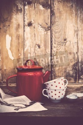 Wall mural Vintage kitchen decor, red enamel coffee pot and cups with polka dots on an old wooden board background with copy space. Rustic home decor.