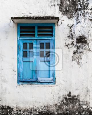 Vivid blue wooden window and grunge wall