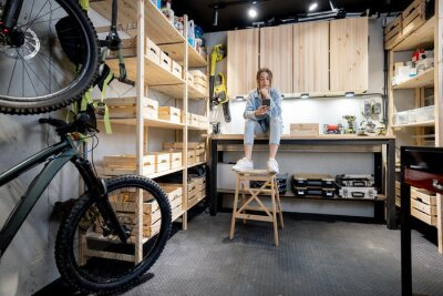 Wall mural Well equipped home workshop with bicycles, wooden shelves and woman sitting on a workbench