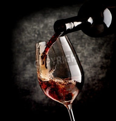 Wall mural Wine pouring in wineglass on a black background