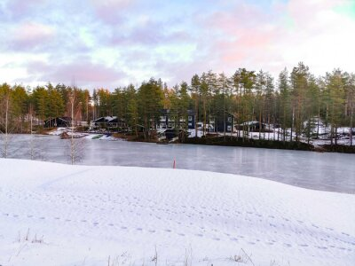 Wall mural Winter landscape with iced lake and pine forest in Finland
