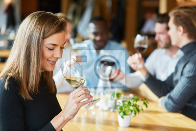 Wall mural Woman is drinking a glass of wine on a wine tasting