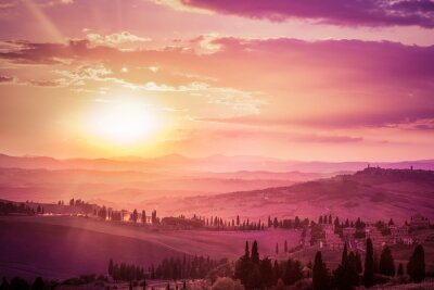 Wall mural Wonderful Tuscany landscape with cypress trees, farms and medieval towns, Italy. Pink and purple sunset