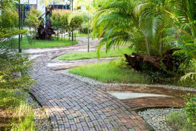 Wall mural Garden walking way made of clay brick in the pleasant morning light