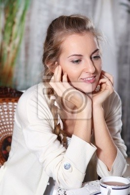 Young blond girl with tea in the cafe