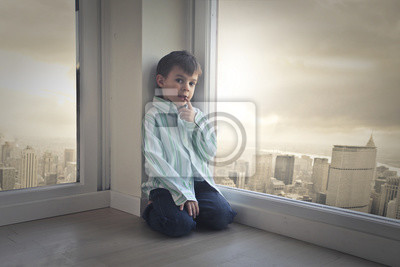 Young child sitting in the corner of a room