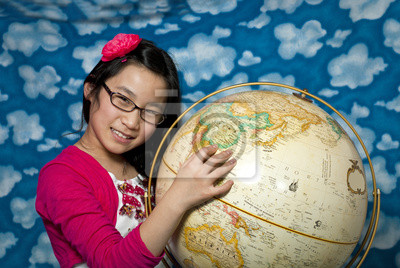 Wall mural Young girl points to China on a globe