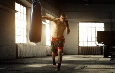 Wall mural Young man boxing workout in an old building