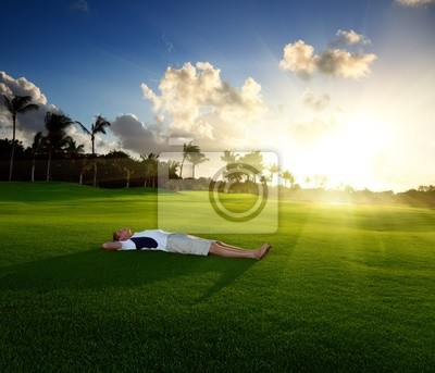 young man relax on green grass
