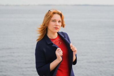 young red-haired girl in a blue coat walking in a park on the city's waterfront