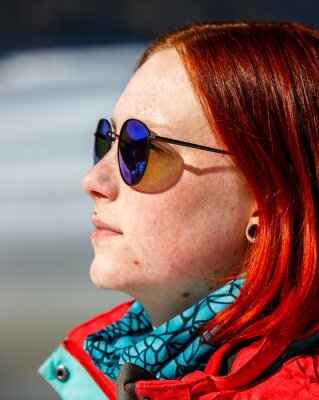 young red head girl with reflecting blue sunglasses out on a sunny winter day