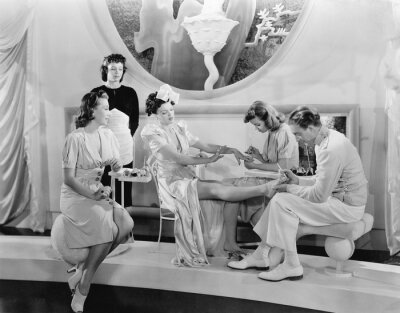 Wall mural Young woman being pampered by three women and a man