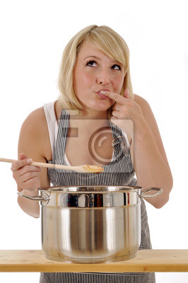 Young woman cooking and seasoning