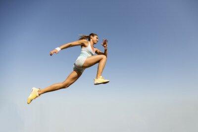 Wall mural Young woman taking long jump