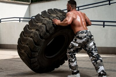 Poster A muscular man participating in a cross fit workout