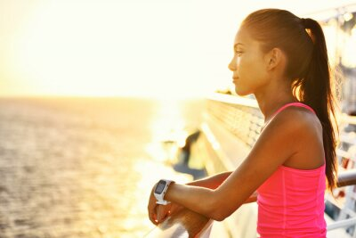 Poster Active woman relaxing after run on cruise ship looking at the sea during summer holidays. Asian runner girl wearing smartwatch heart rate activity monitor living a healthy lifestyle.
