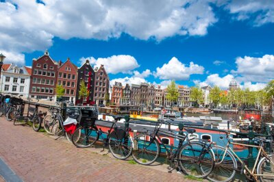 Poster Amsterdam, the Netherlands-April 27: Traditional Amsterdam cityscape with medival houses, bikes on the bridge on April 27,2015. Amsterdam is the most populous city of the Kingdom of the Netherlands.
