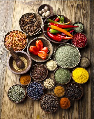 Poster Assortment of spices in wooden bowl background
