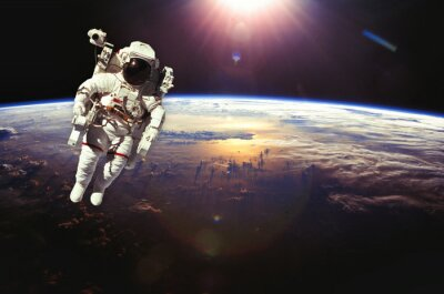 Poster Astronaut in outer space above the earth during sunset. Elements