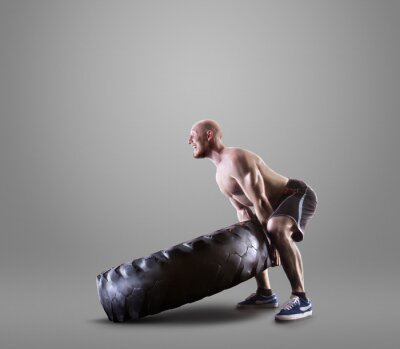 Poster Athletic young man lifting a tire on gray studio background
