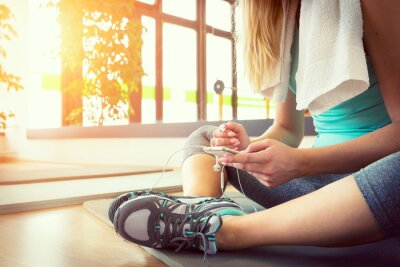 Poster Attractive blond woman with smart phone, resting after gym workout