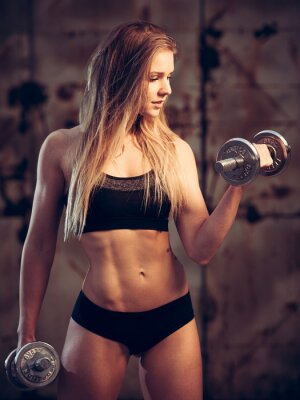 Poster attractive young woman working out with dumbbells in an abandone