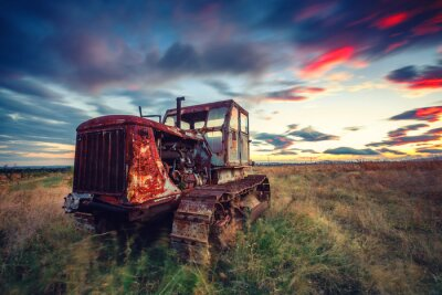 Poster Beautiful sunset over field and old rusty tractor