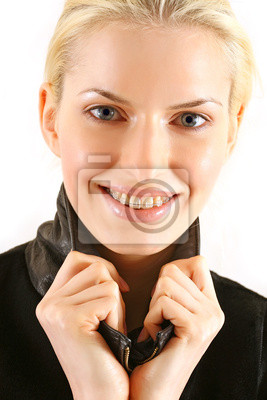 Beautiful young blonde with brackets on teeth in white