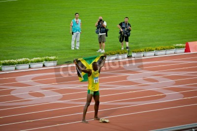 Poster Beijing - Aug 16: Usain Bolt celebrates holding the Jamaican flag after setting new world 100 meter record  for men
