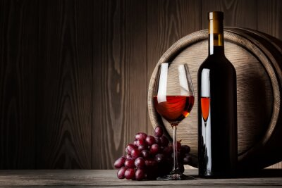 Poster Black bottle and glass of red wine with grapes and barrel