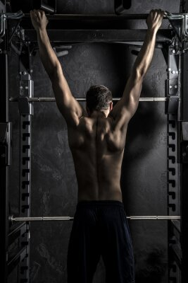 Poster Bodybuilding, Young Athletic Strong Man showing Back Muscles working on Fitness Bar, Strong Contrast with Desaturated Grunge filter