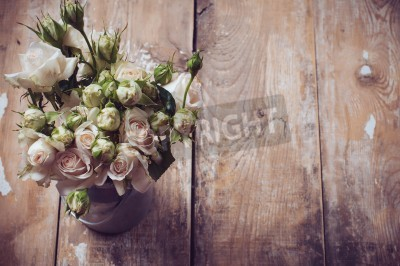 Poster Bouquet of roses in metal pot on the wooden background, vintage style