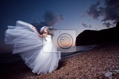 Bride posing showing her wedding dress on sunset beach