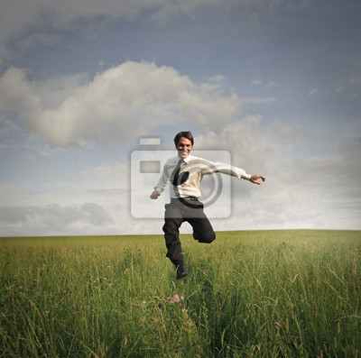 Businessman running in a field