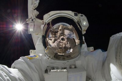 Poster close up view of floating astronaut with a reflection of the space station showing (some elements courtesy of nasa)