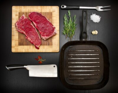 Poster composition with raw rib and kitchen tools on black wood