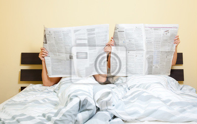 couple newspaper in bed